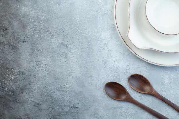 Elegancki pusty biały zestaw obiadowy i drewniane łyżki po lewej stronie na izolowanej szarej powierzchni z wolną przestrzenią