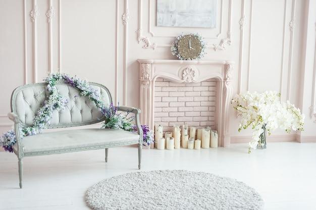 Elegancki różowy pastelowy kominek ozdobiony wiosennymi kwiatami, świecami.