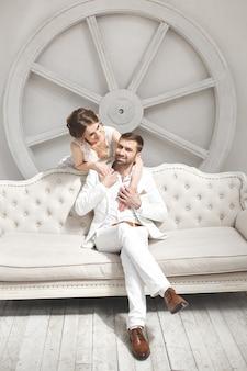 Elegancki ślub para pana młodego i panny młodej pozowanie studio biały. szczęśliwa para śmiejąc się. biała sukienka. biały garnitur. młodzież. ślub. żyrandol. sofa. drzwi.