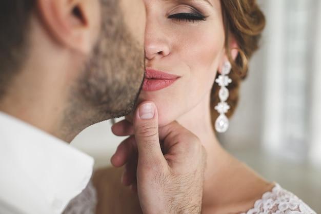 Elegancki ślub para pana młodego i panny młodej, pozowanie w białym studio. szczęśliwa para się śmieje. biała sukienka. biały garnitur. młodość. ślub. żyrandol. sofa. drzwi.