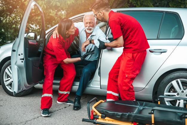 Elegancki starszy mężczyzna z objawami zawału serca siedzi w samochodzie, pracownicy pogotowia ratunkowego próbują mu pomóc.