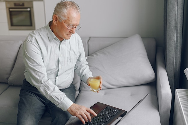 Elegancki stary człowiek siedzi w domu i używa laptopa