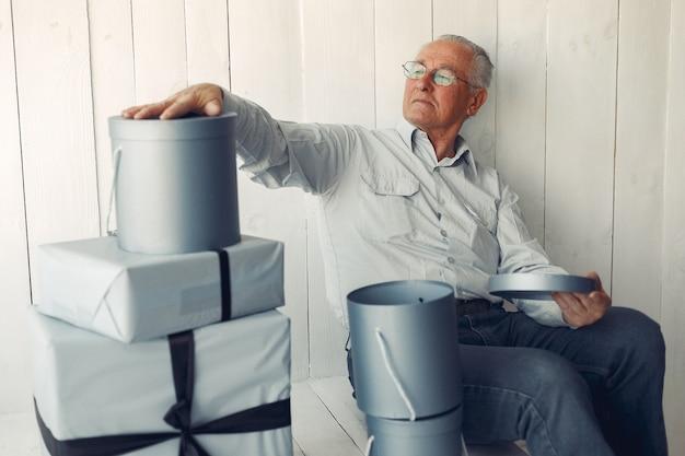 Elegancki stary człowiek siedzi w domu z prezentami