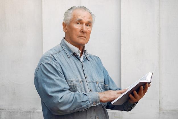 Elegancki stary człowiek stojący z książką
