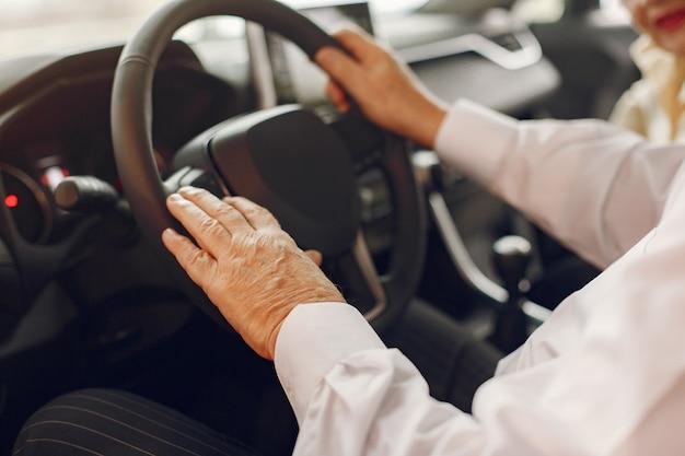 Elegancki stary człowiek w salonie samochodowym