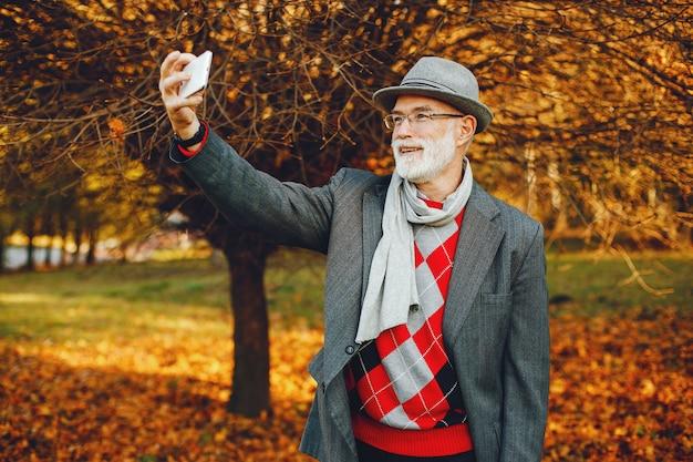 Elegancki stary człowiek w słonecznym jesień parku
