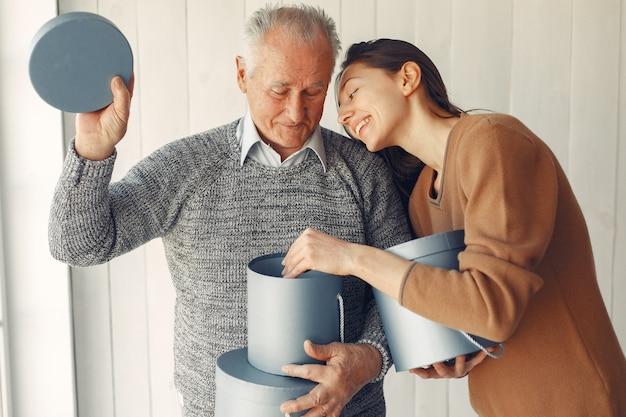 Elegancki starzec stojący w domu ze swoją wnuczką
