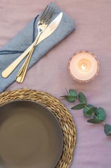 Elegancki stół ustawienie purpurowe płótno ciemna płyta rattan coaster sztućce serwetka świeca