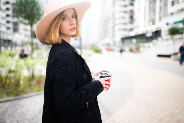 Elegancki stylowy blond krótkie włosy dziewczyna w kapeluszu z kawą na tle ulicy