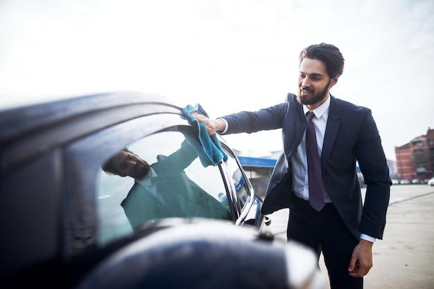 Elegancki stylowy młody brodaty mężczyzna w garniturze do czyszczenia bocznego okna samochodu za pomocą niebieskiej ściereczki z mikrofibry.