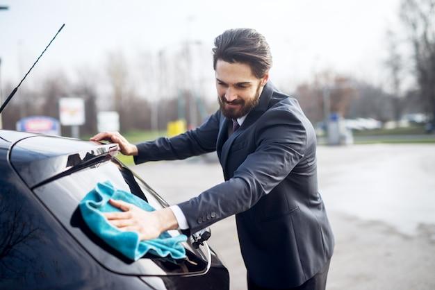 Elegancki stylowy młody brodaty mężczyzna w garniturze do czyszczenia tylnej szyby samochodu za pomocą niebieskiej ściereczki z mikrofibry.