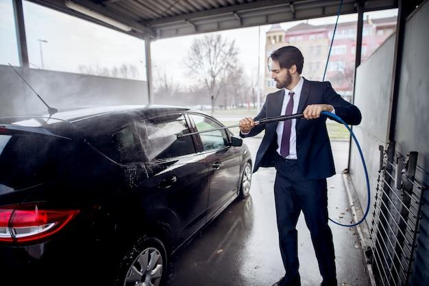 Elegancki, stylowy, młody, skoncentrowany mężczyzna w garniturze czyszczącym stronę samochodu z pistoletem na wodę na myjni samoobsługowej.