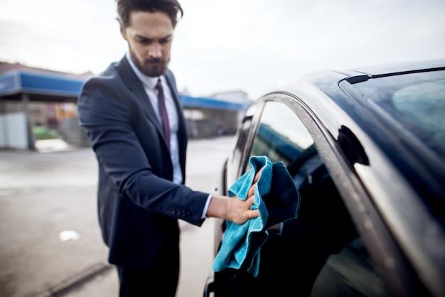Elegancki stylowy poważny młody brodaty mężczyzna w garniturze do czyszczenia bocznego okna samochodu za pomocą niebieskiej ściereczki z mikrofibry.