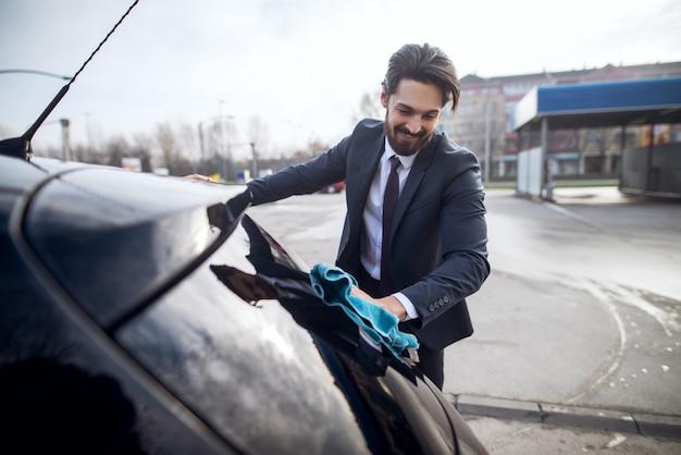 Elegancki stylowy wesoły młody brodaty mężczyzna w garniturze do czyszczenia tylnej szyby samochodu za pomocą niebieskiej ściereczki z mikrofibry.