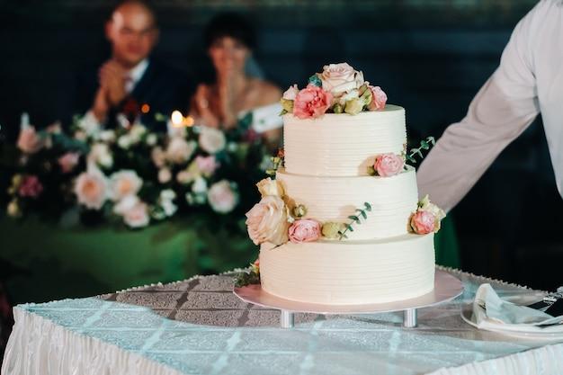 Elegancki tort weselny na weselu w trzech poziomach.