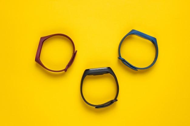 Elegancki zegarek z wymiennymi bransoletkami na żółtym tle. monitor aktywności. nowoczesne gadżety