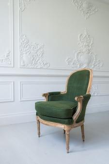 Elegancki zielony fotel w luksusowym, czystym, jasnym białym wnętrzu