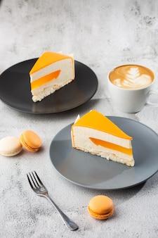 Eleganckie ciasto z kokosem, marakują, mango i bananami, pokryte polewą czekoladową. plasterek pomarańczowy warstwowe ciasto na tle marmuru. tapeta do cukierni lub menu kawiarni. pionowy.