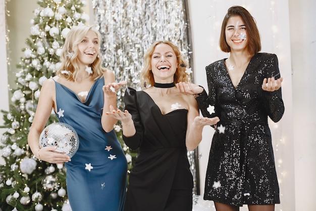 Eleganckie damy w pobliżu choinki. kobiety w eleganckich ubraniach.