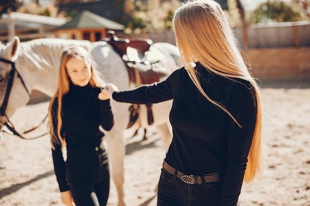 Eleganckie dziewczyny z koniem na ranczo