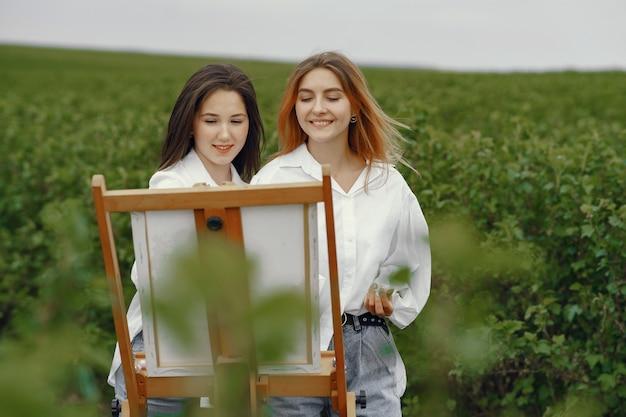 Eleganckie i piękne dziewczyny malujące w polu