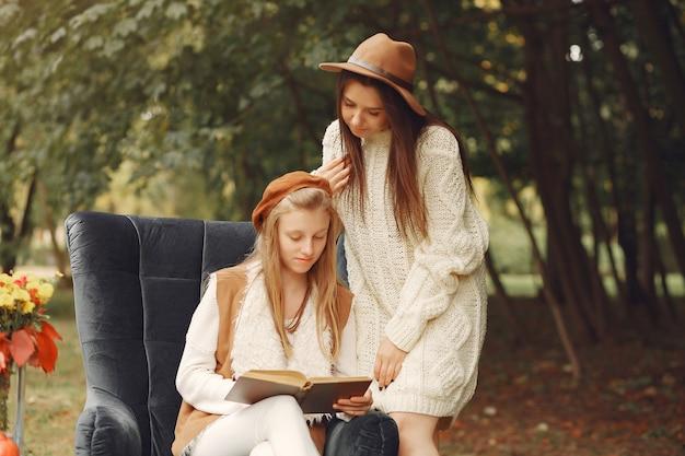 Eleganckie i stylowe dziewczyny siedzą na krześle w parku