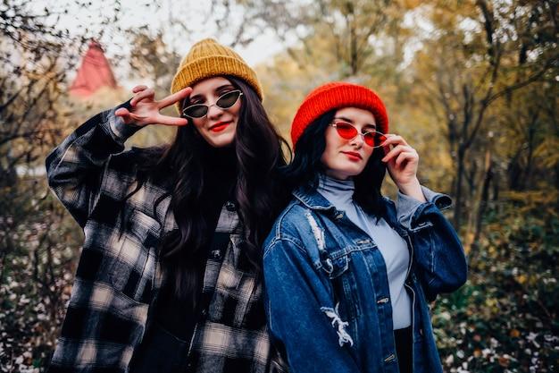 Eleganckie i stylowe dziewczyny siedzą w jesiennym parku