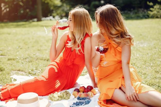 Eleganckie i stylowe dziewczyny w letnim parku