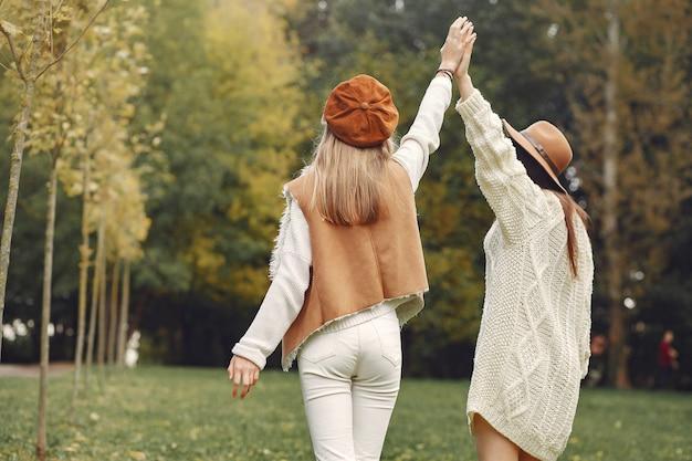 Eleganckie i stylowe dziewczyny w parku