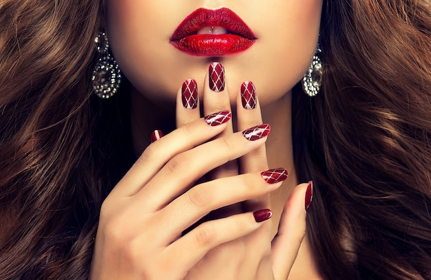 Eleganckie kobiece dłonie z profesjonalnie wykonanym manicure na paznokciach.piękne, smukłe i wdzięczne palce przed zgrabnymi ustami pomalowane wiśniową szminką.manicure, biżuteria i kosmetyki.