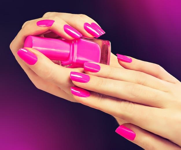 Eleganckie kobiece dłonie z różowym manicure na paznokciach. piękne, smukłe i wdzięczne palce trzymają buteleczkę z różowym lakierem do paznokci. manicure i kosmetyki.