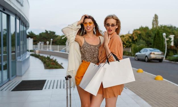 Eleganckie kobiety po wyjściu z podróży i zakupach pozują na świeżym powietrzu w pobliżu lotniska