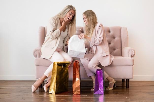 Eleganckie kobiety sprawdzające torby na zakupy