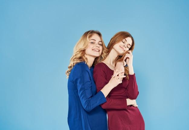 Eleganckie kobiety ubierają uściski lifestyle studio elegancki styl niebieskie tło