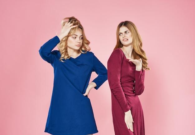 Eleganckie kobiety w sukniach mody dekoracji komunikacji różowym tle