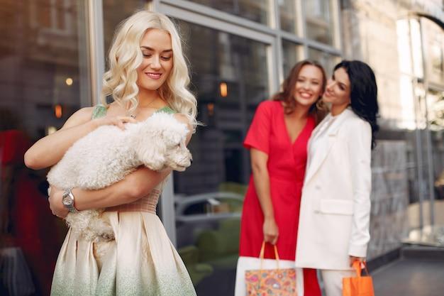 Eleganckie kobiety z małym psem w mieście