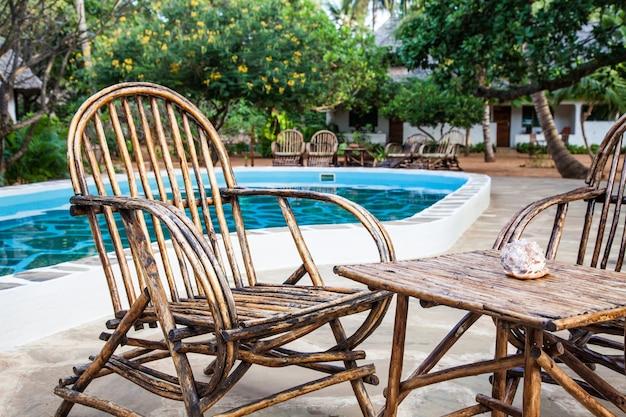 Eleganckie krzesła wykonane z drewna w pobliżu basenu w kenijskim ogrodzie