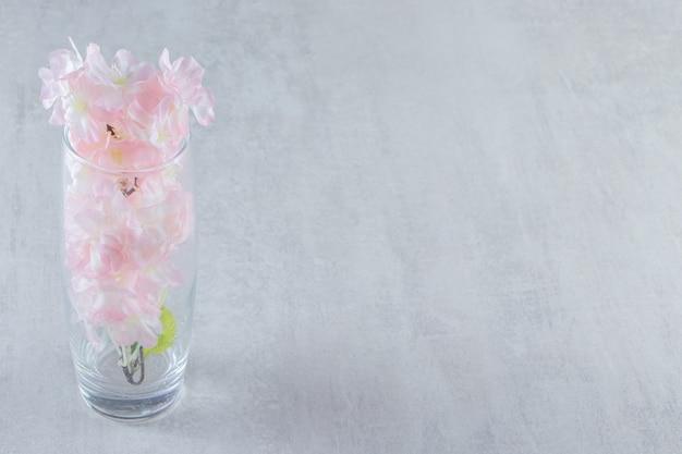 Eleganckie kwiaty w dzbanku, na białym stole.
