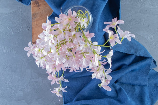 Eleganckie kwiaty w dzbanku na desce na kawałku materiału, na białym tle. zdjęcie wysokiej jakości