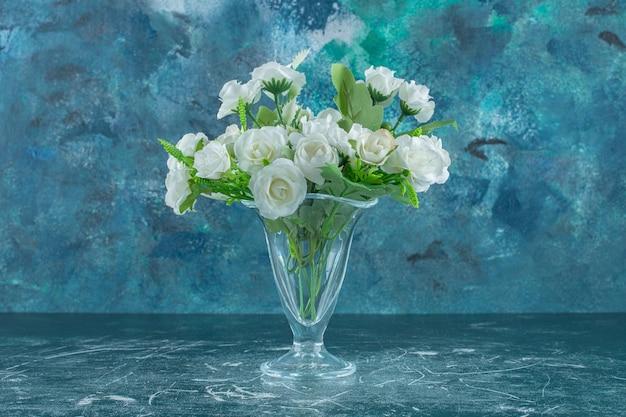 Eleganckie kwiaty w szklanym dzbanku na białym stole.