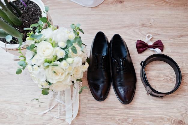 Eleganckie męskie buty ślubne, bukiet, pasek i krawat na pana młodego rano.