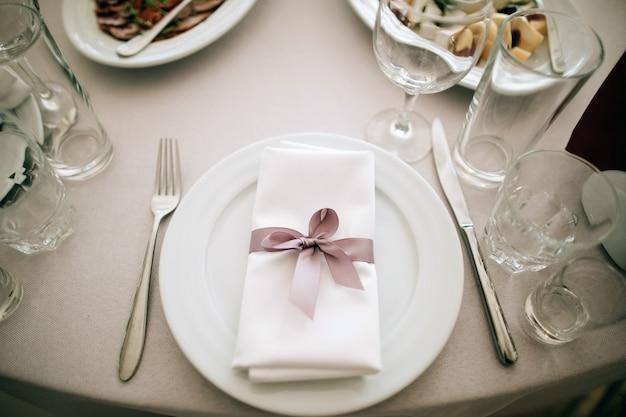 Eleganckie nakrycie stołu na weselną kolację w restauracji