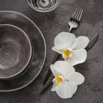 Eleganckie nakrycie stołu z dzianinową szarą serwetką, sztućcami, ceramicznymi talerzami, szklankami i białymi kwiatami orchidei na ciemnym stole. świąteczna nowoczesna dekoracja stołu. romantyczna kolacja.