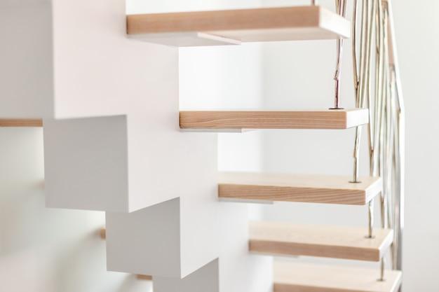 Eleganckie, nowocześnie zaprojektowane schody w białym nowoczesnym pokoju w luksusowym apartamencie.