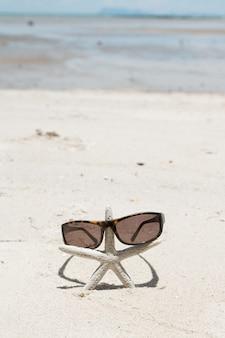 Eleganckie okulary przeciwsłoneczne i rozgwiazda na białej, piaszczystej plaży