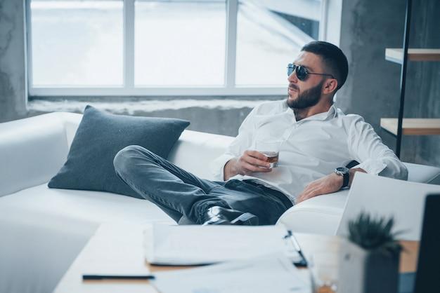 Eleganckie pozowanie. młody z włosami mężczyzna siedzi na kanapie w biurze w okularach przeciwsłonecznych