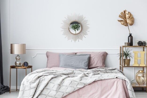 Eleganckie, różowo-złote wnętrze sypialni z lustrem w kształcie słońca nad łóżkiem z poduszkami i kocem