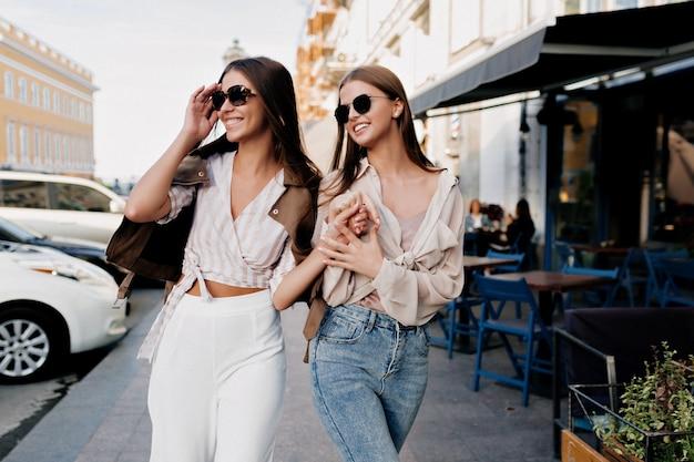 Eleganckie stylowe kobiety w modnym stroju po zakupach po mieście chodzą po mieście.