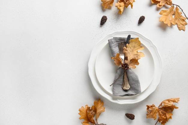 Eleganckie ustawienie stołu jesienią z suchymi liśćmi i białym talerzem na białym z miejscem na kopię