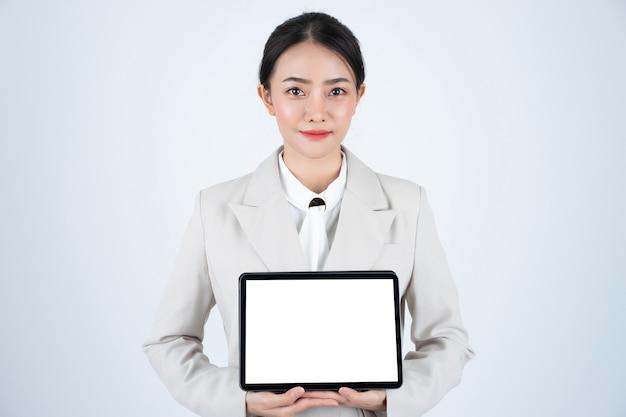 Eleganckiego azjatykciego bizneswomanu przedstawienia cyfrowa pastylka z białym pustym ekranem